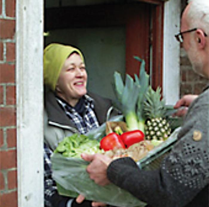 Lieferservice direkt vor die Haustür - Übergabe eines Obst- und Gemüsekorbes